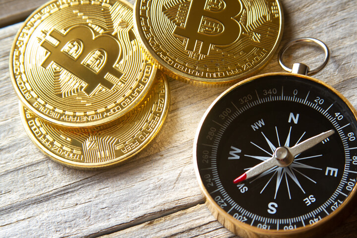 Three bitcoins arranged with navigational compass on weathered wood plank