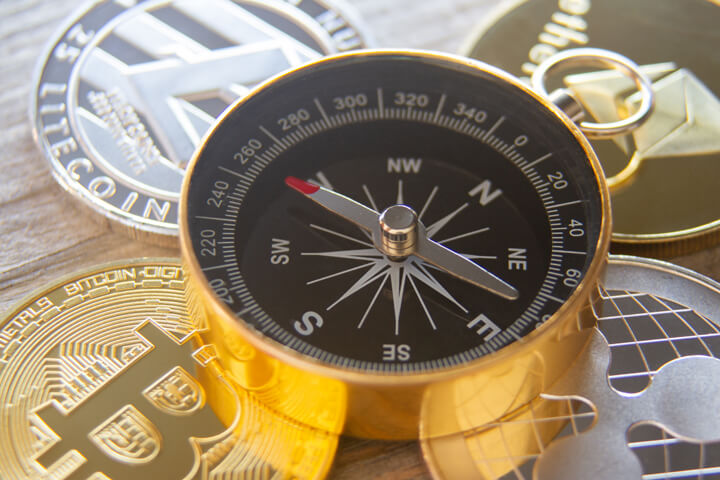 Four cryptocurrency coins with navigational compass on top