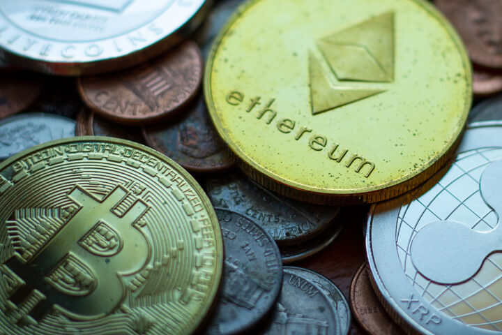 Ethereum, Bitcoin, Litecoin, and Ripple XRP coins with tarnish lying on assorted U.S. currency coins