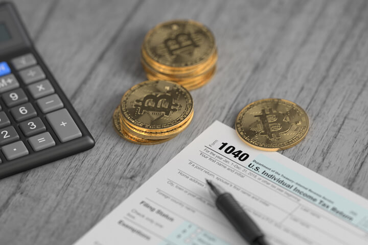 Stacks of Bitcoins surrounding IRS 1040 tax form with ballpoint pen and calculator concept for paying cryptocurrency taxes