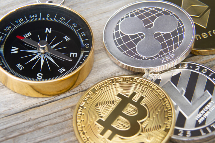 Navigational compass next to Bitcoin, Litecoin, Ripple, and Ethereum crypto coins