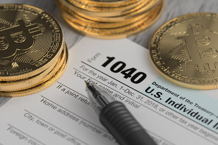 Stacks of Bitcoins surrounding IRS 1040 tax form with ballpoint pen concept for paying cryptocurrency taxes