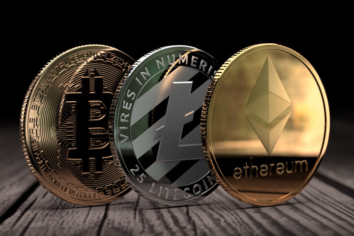 Ethereum, Litecoin, and Bitcoin standing on edge on wood surface