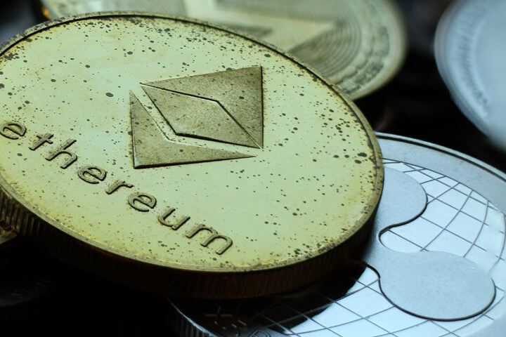 Close up photo of tarnished crypto coins including Ethereum, Ripple XRP, and Monero cryptocurrencies