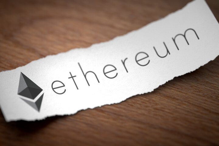 Ethereum cryptocurrency logo printed on torn piece of black scrap paper lying on woodgrain surface