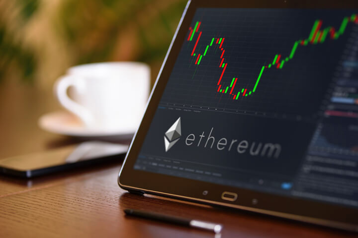 Tablet on desk with coffee cup and cell phone showing Ethereum cryptocurrency logo and stock price candlestick chart