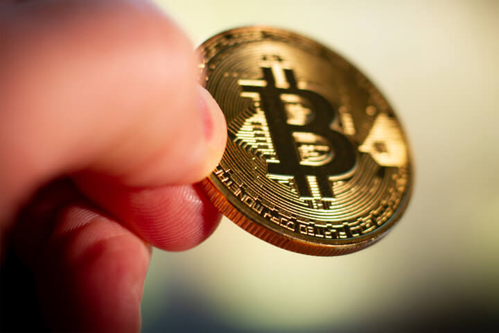 Photo of two fingers pinching a Bitcoin with short depth-of-field and background bokeh blur