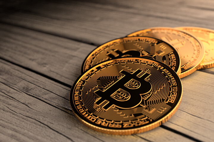 Four Bitcoins in a curved path on weathered wood planks with top right lighting