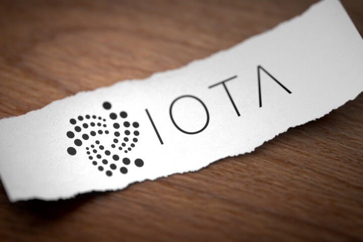 Iota cryptocurrency logo printed on torn piece of white scrap paper lying on woodgrain surface