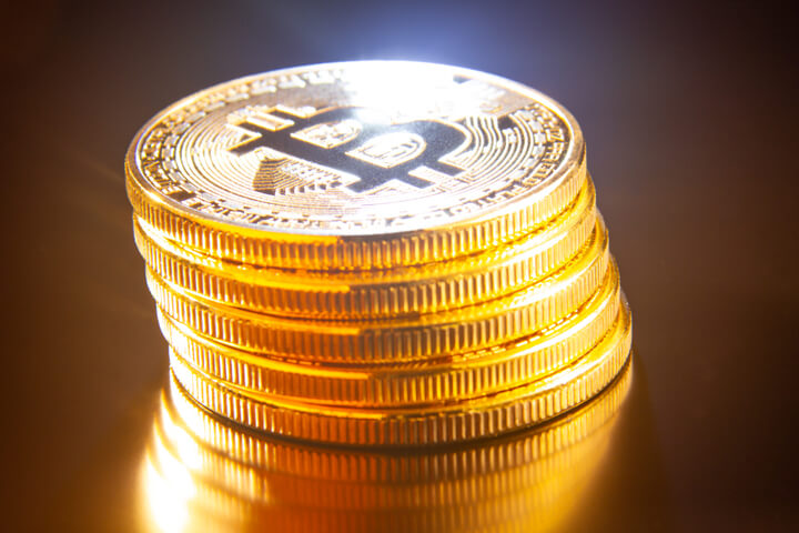 Leaning stack of bitcoins on reflective textured surface with light flare