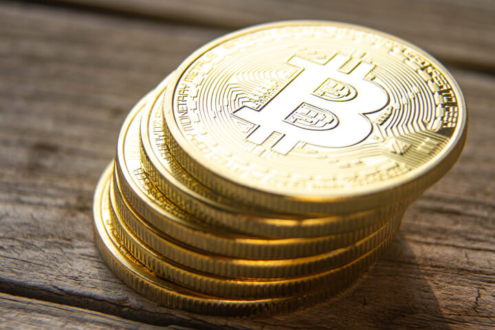View from top of leaning stack of bitcoins on wood plank background