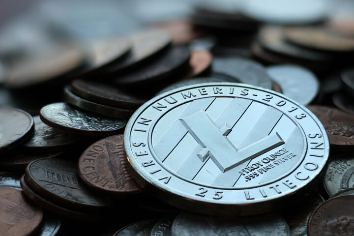 Photo of Litecoin cryptocurrency coin on top of an assorted pile of U.S. currency coins