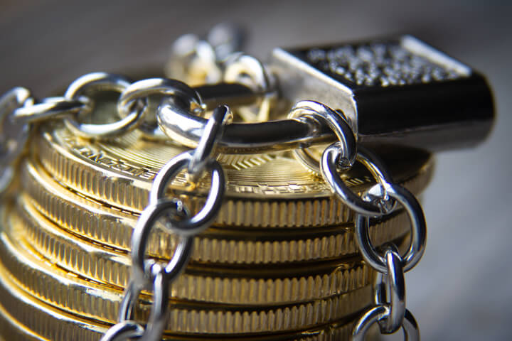 Stack of Bitcoins wrapped with chains and locked with a padlock