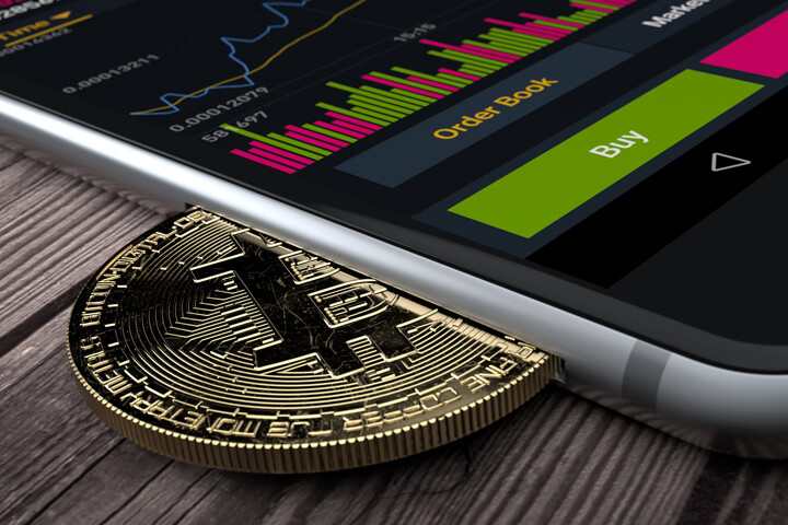 iPhone with Bitcoin inserted into slot concept for mobile Bitcoin apps, profits, or trades