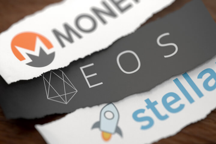 Monero, EOS, and Stellar altcoin cryptocurrency logos printed on torn piece of white scrap paper lying on woodgrain surface