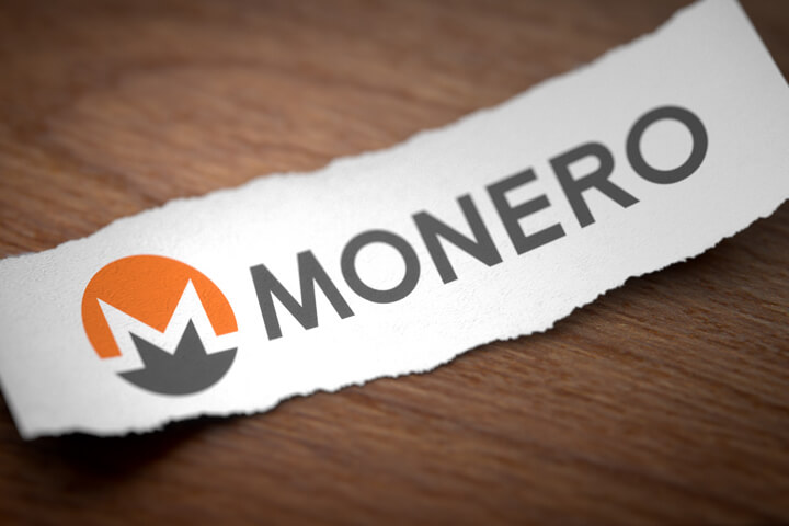 Monero altcoin cryptocurrency logo printed on torn piece of scrap paper on woodgrain surface