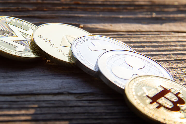 Row of cryptocurrency coins in morning light with hard shadows