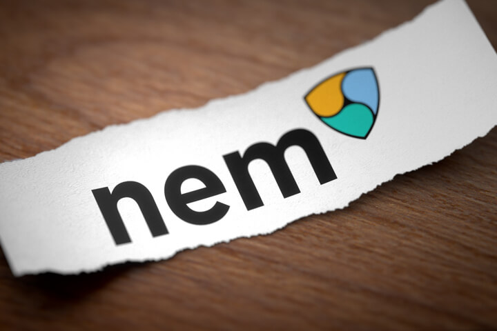 Nem altcoin cryptocurrency logo printed on torn piece of scrap paper on woodgrain surface