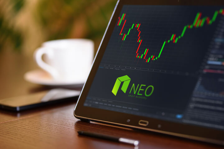 Tablet on desk with coffee cup and cell phone showing Neo cryptocurrency logo and stock price candlestick chart