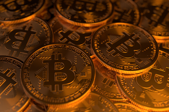 Large random pile of Bitcoins illuminated with soft golden light from side