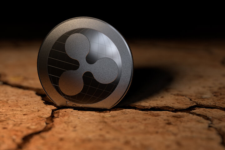 Ripple crypto coin stuck in crack left from dry desert mud