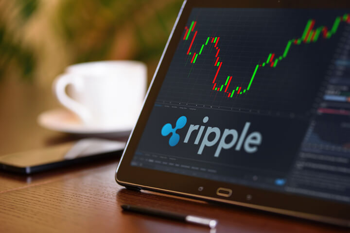 Tablet on desk with coffee cup and cell phone showing Ripple cryptocurrency logo and stock price candlestick chart