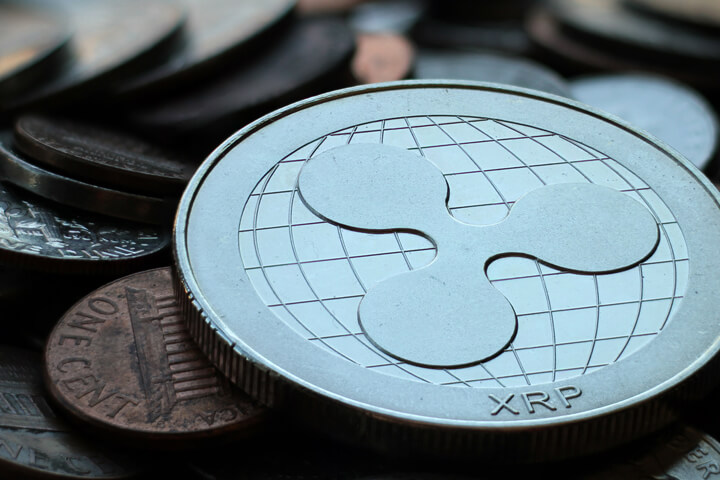 Close up photo of Ripple XRP cryptocurrency coin on top of an assorted pile of tarnished U.S. currency coins