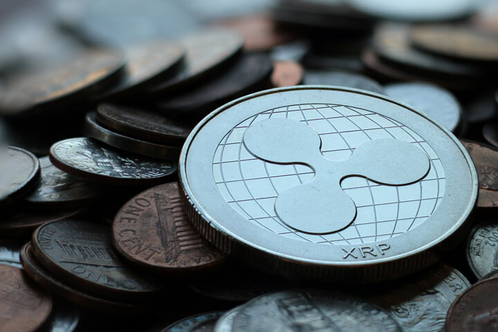 Photo of Ripple XRP cryptocurrency coin on top of an assorted pile of tarnished U.S. currency coins with depth-of-field blur