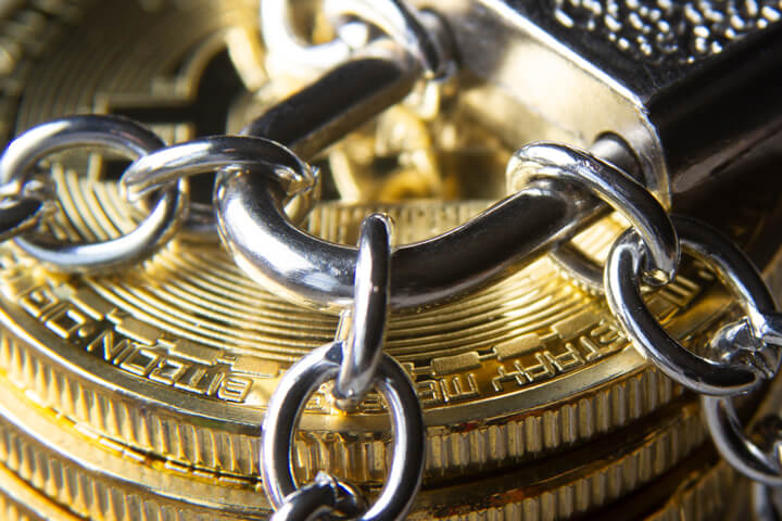 Close up photo of a stack of Bitcoins secured by chains and a padlock