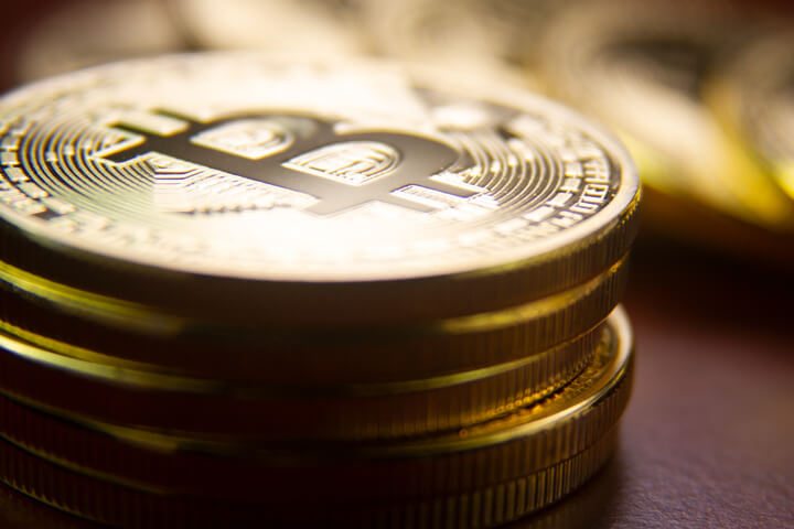 Stack of bitcoins in foreground with row of coins blurred in background