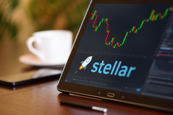 Tablet On Desk With Coffee Cup And Cell Phone Showing Stellar Cryptocurrency Logo Stock Price