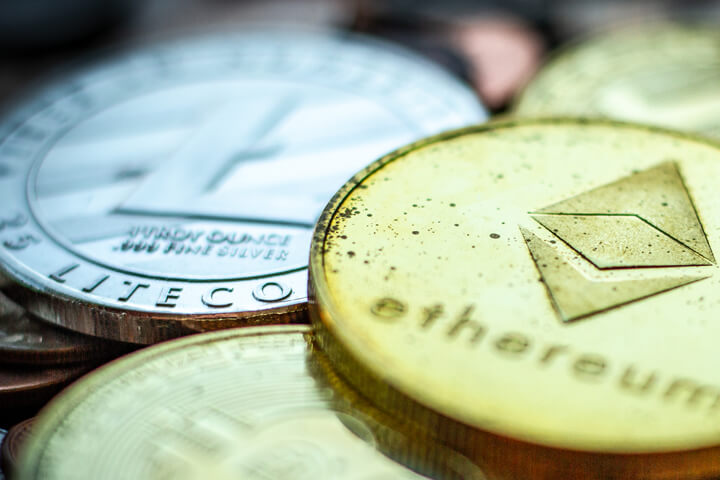 Tarnished Ethereum, Litecoin, Bitcoin, and Monero coins on assorted U.S. currency coins with sharp depth-of-field blur