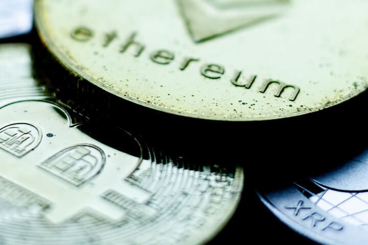 Tarnished Ethereum, Bitcoin, and XRP coins close up photo showing sharp contrast and metal tarnish