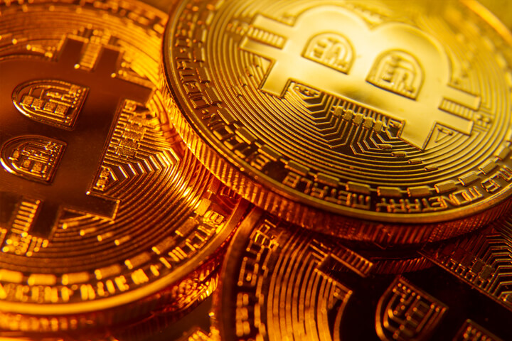 Three gold bitcoins with spotlight focus