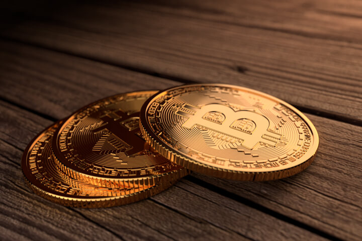 Three Bitcoins stacked in a row on stained wood planks