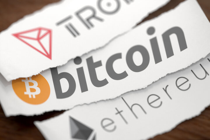 Tron, Bitcoin, and Ethereum cryptocurrency logos printed on torn pieces of white scrap paper on woodgrain surface
