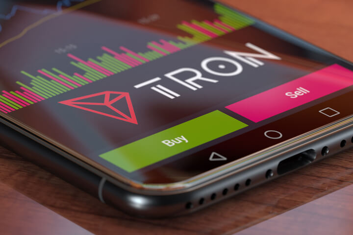 Tron exchange app on iPhone X screen showing Tron logo, trading volume, and option to buy or sell cryptocurrency