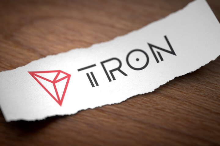 Tron altcoin cryptocurrency logo printed on torn piece of scrap paper on woodgrain surface