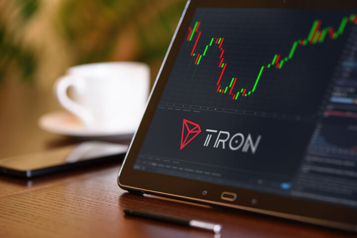 Tablet on desk with coffee cup and cell phone showing Tron cryptocurrency logo and stock price candlestick chart