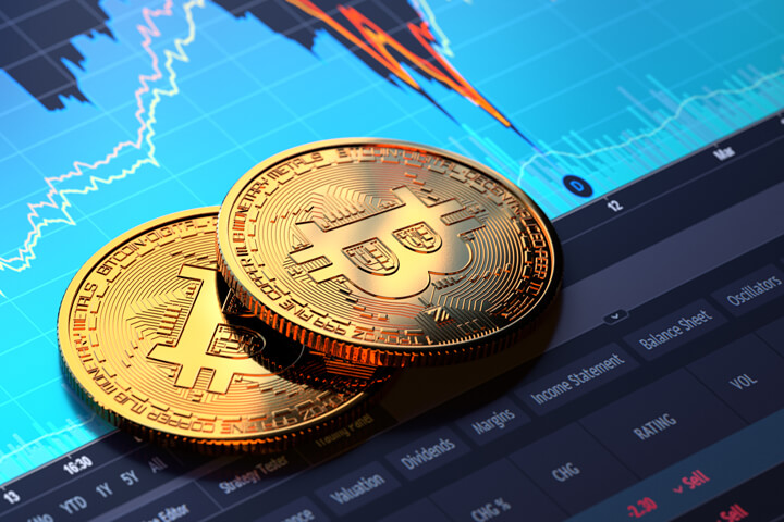Two Bitcoins on laptop screen showing BTC price area chart with sharp decline and recovery