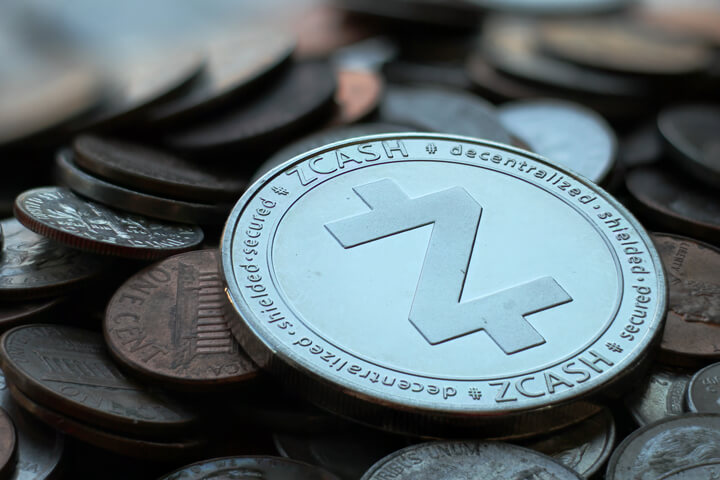 Zcash cryptocurrency coin on pile of assorted tarnished U.S. currency coins with sharp depth-of-field blur