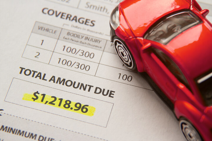 Toy car on auto insurance billing statement showing amount due