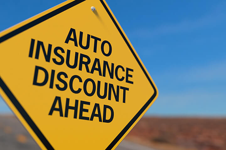 Yellow road sign reading Auto Insurance Discount Ahead