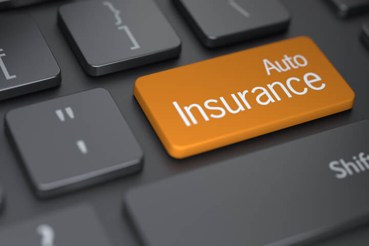 Laptop keyboard with large orange auto insurance key concept for buying auto insurance online