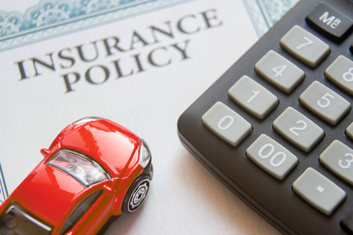 Auto insurance policy with calculator and small red toy car