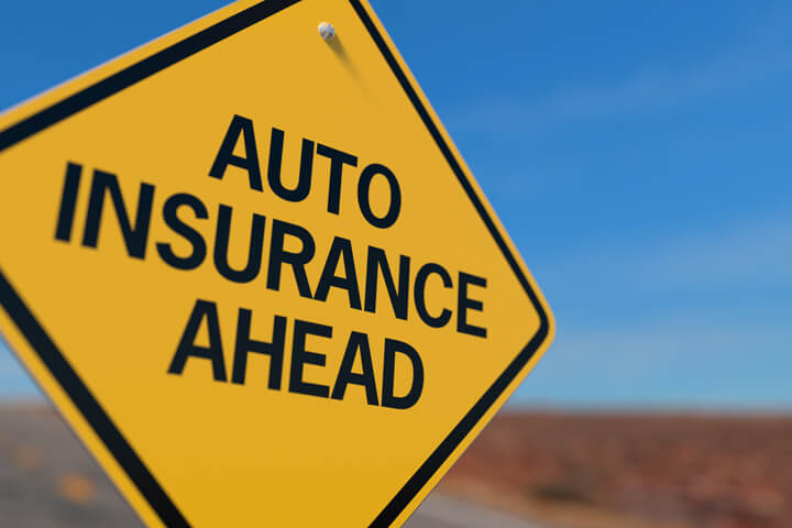 Yellow road sign stating Auto Insurance Ahead