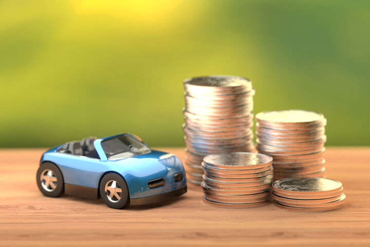 Toy convertible car next to stacks of coins symbolizing the cost of car insurance or vehicle cost of ownership