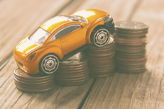 Vintage photo of small toy car climbing increasing stacks of coins