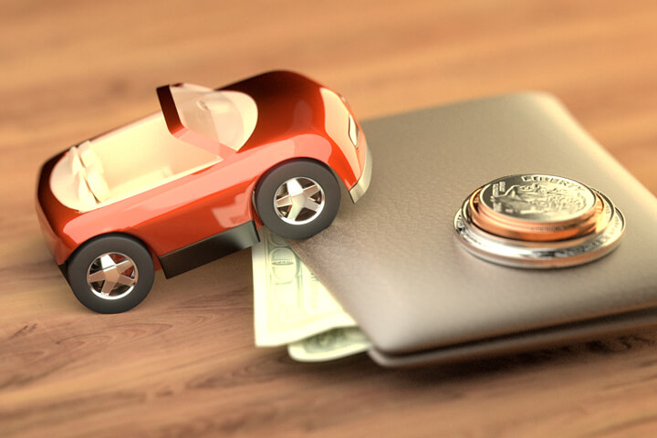 Toy car climbing wallet with small stack of coins on top symbolizing the cost of auto insurance