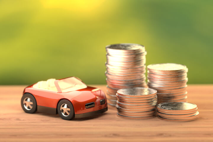Small red toy car next to stacks of coins on wood table with nature background
